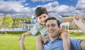 Mixed Race Father and Son Piggyback in Front of House Stock Photos