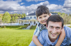 Mixed Race Father and Son Piggyback in Front of House Royalty Free Stock Photos