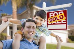 Mixed Race Father, Son Piggyback, Front of House, Sold Sign. Mixed Race Father and Son Celebrating with a Piggyback in Front Their House and Sold Real Estate Stock Photos
