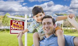 Mixed Race Father, Son Piggyback, Front of House, Sold Sign. Mixed Race Father and Son Celebrating with a Piggyback in Front Their House and Sold Real Estate Royalty Free Stock Photo