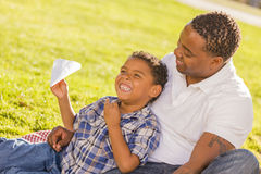 Mixed Race Father and Son Playing with Airplanes. Happy African American Father and Mixed Race Son Playing with Paper Airplanes in the Park stock photography
