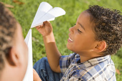 Mixed Race Father and Son Playing Paper Airplanes. Happy Mixed Race Father and Son Playing with Paper Airplanes in the Park royalty free stock photo