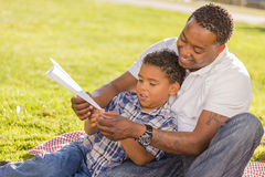 Mixed Race Father and Son Playing Paper Airplanes. Happy African American Father and Mixed Race Son Playing with Paper Airplanes in the Park royalty free stock photos