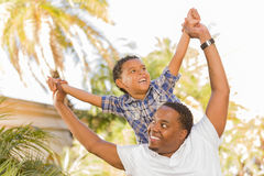 Mixed Race Father and Son Playing Piggyback Stock Photos