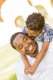 Mixed Race Father and Son Playing Piggyback Stock Photo