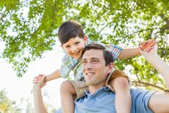 Mixed Race Father and Son Playing Piggyback Together Outdoors. Mixed Race Father and Son Playing Piggyback Together in the Park Stock Image