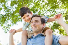 Mixed Race Father and Son Playing Piggyback Together in the Park. Mixed Race Father and Son Playing Piggyback Together at the Park Stock Image