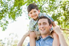 Mixed Race Father and Son Play Piggyback Together in the Park. Mixed Race Father and Son Playing Piggyback Together in the Park Outdoors Stock Image
