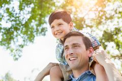 Mixed Race Father and Son Playing Piggyback Together in the Park. On a Sunny Afternoon Royalty Free Stock Photography
