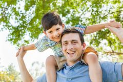 Mixed Race Father and Son Playing Piggyback Together in the Park. Mixed Race Father and Son Playing Piggyback Together Under the Trees in the Park Stock Photography