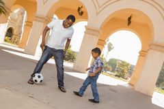 Mixed Race Father and Son Playing Soccer in the Courtyard Royalty Free Stock Photo