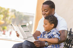 Mixed Race Father and Son Reading Park Brochure Royalty Free Stock Image