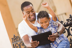Mixed Race Father and Son Using Touch Pad Tablet. Happy African American Father and Mixed Race Son Having Fun Using Touch Pad Computer Tablet Outside Royalty Free Stock Images