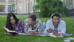 Mixed-race fellows having rest on lawn on college campus, enjoying hobbies. Stock footage stock video footage