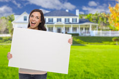 Mixed Race Female with Blank Sign In Front of House. Excited Mixed Race Female with Blank Sign In Front of Beautiful House Royalty Free Stock Image