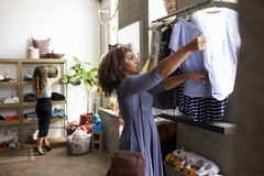 Mixed race female customer clothes shopping in a boutique Royalty Free Stock Image