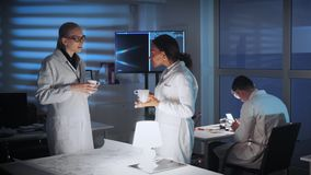 Mixed race female engineers in white coats discussing something in modern lab. There is a TV screen in the background stock video footage