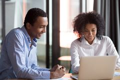 Mixed-race mentor manager consulting african client teaching employee with laptop. Mixed race female mentor hr manager consulting african american client royalty free stock photography