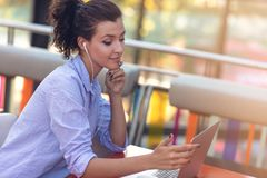 Mixed race female performing business negotiations on video chat. Telecommuting concept. Businesswoman working remotely at cafe with headset and laptop. Mixed royalty free stock images