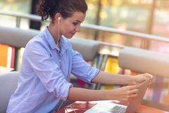 Mixed race female performing business negotiations on video chat. Telecommuting concept. Businesswoman working remotely at cafe with headset and laptop. Mixed royalty free stock photo