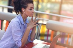 Mixed race female performing business negotiations on video chat. Telecommuting concept. Businesswoman working remotely at cafe with headset and laptop. Mixed stock photo