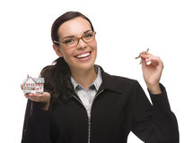 Mixed Race Female Presenting Keys and Holding a Small House Stock Photo