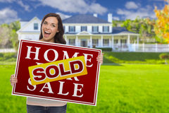 Mixed Race Female with Sold Sign In Front of House. Excited Mixed Race Female with Sold Home For Sale Real Estate Sign In Front of Beautiful House Stock Image