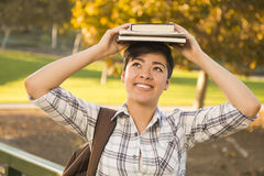 Mixed Race Female Student Holding Books on Her Head stock image
