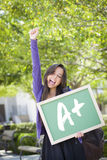 Mixed Race Female Student Holding Chalkboard With A+ Written Royalty Free Stock Photos