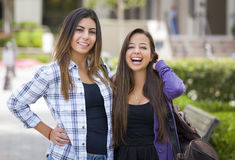Mixed Race Female Students Carrying Backpacks on School Campus Stock Photo