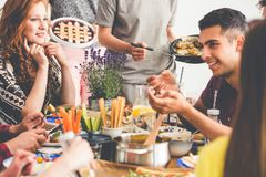 Mixed-race friends enjoying vegetarian lunch. Group of mixed-race friends enjoying vegetarian lunch at restaurant, eating salads, greens and vegan desserts stock photography