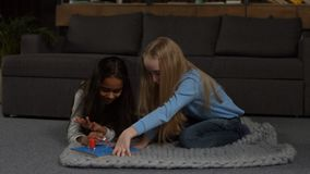 Mixed race girl applying nail polish to her friend stock video