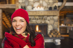 Mixed Race Girl Enjoying Warm Fireplace In Rustic Cabin Stock Image