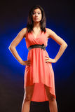 Mixed race girl in party dress on blue. Party clothing evening fashion concept - Portrait attractive fashion woman, mixed race girl in orange elegant dress dark Royalty Free Stock Photos