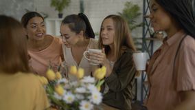 5 mixed race girlfriends drink tea / coffee in the kitchen. women having fun and chatting 4K. 5 mixed race girlfriends drink tea / coffee in the kitchen. women stock footage