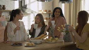 5 mixed race girlfriends drink tea / coffee in the kitchen. women having fun and chatting 4K stock footage