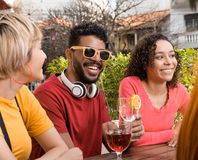 Mixed race group bonding and drinking at cafe bar outdoor. Spring, warm, togetherness, lifestyle, diversity concept. Happy friends having a great time at royalty free stock images