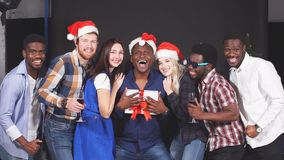 Mixed race group of friends at Christmas party, smiling and looking in camera, slow motion. stock video footage