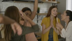 Mixed race group of 5 friends having fun in the kitchen. girls dance and sing while cooking 4K. Mixed race group of 5 friends having fun in the kitchen. girls stock video footage