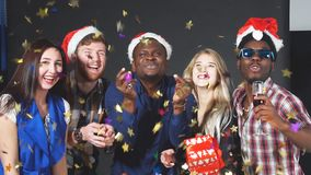 Mixed race group of young people blowing golden confetti from hands. Mixed race group of young people blowing golden confetti from hands stock footage