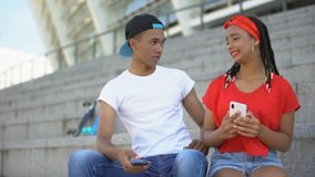 Mixed-race guy jealous of girlfriend chatting in social networks with other boys. Stock footage stock footage