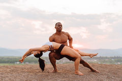 Mixed race gymnastic couple with perfect bodies in sportswear dancing on mountains landscape background. Pink sunset sky Royalty Free Stock Photos