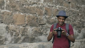 Mixed race happy tourist man taking photo on his dslr camera standing near famous building in Europe stock video footage