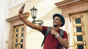 Mixed race happy tourist man taking selfie photo on his smartphone camera standing near famous building in Europe stock photos