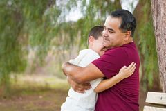 Mixed Race Hispanic Father Hugging His Son At The Park stock photo
