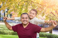 Mixed Race Hispanic and Caucasian Son and Father Having Fun At The Park. Mixed Race Hispanic and Caucasian Son and Father Having Fun Playing Piggy Back At The royalty free stock photography