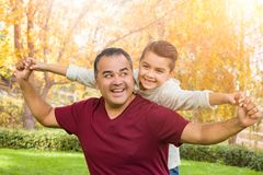 Mixed Race Hispanic and Caucasian Son and Father Having Fun At The Park. Mixed Race Hispanic and Caucasian Son and Father Having a Fun Time At The Park stock photos