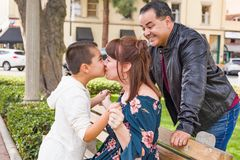 Mixed Race Hispanic Caucasian Son, Mother and Father Give Kisses At The Park. Mixed Race Hispanic and Caucasian Son, Mother and Father Having Fun At The Park royalty free stock photo
