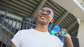 Mixed-race hooligan in sunglasses with skateboard ready for hanging-out, youth. Stock footage stock video