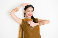 Mixed race Indian girl dancing. Portrait of young mixed race Indian Chinese female dancer in traditional punjabi dress with dancing pose, standing on plain white Stock Image